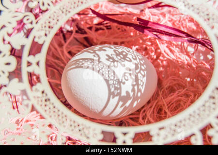 Easter card with egg and white openwork oval frame on coral background, Bright sunlight creates beautiful shadows on white egg, copyspace, top view - Stock Image