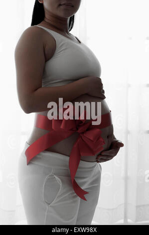 Pregnant woman standing with red ribbon on the abdomen, - Stock Image