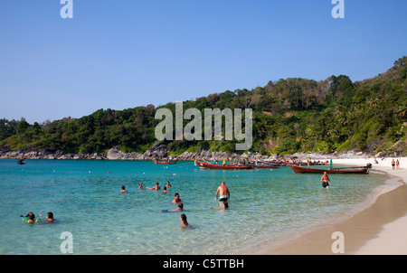 Longtail Boats anchored along Freedom Beach and people swimming in the Andaman Sea . - Stock Image