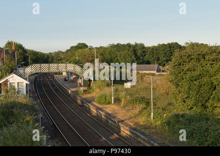 Acle railway station, showing footbridge crossing the tracks on a sunny evening. - Stock Image