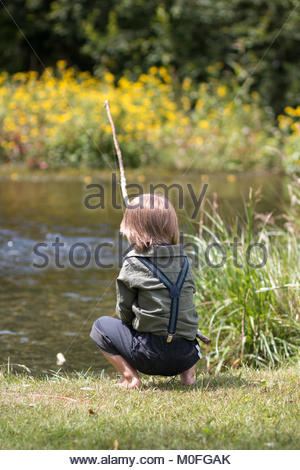 Little boy sitting on a river shore with ild-fashioned fishing rod - Stock Image