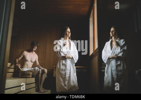 Beautiful woman relaxing in sauna and staying healthy - Stock Image