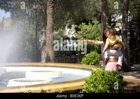 Mother and toddler having fun at the ornamental fountain in Mijas Pueblo, Costa del Sol, Andalucia, Spain - Stock Image