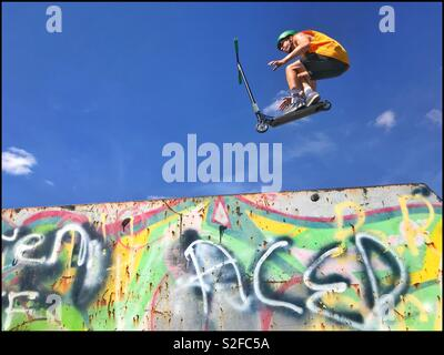 A teenager does an aerial scooter trick at a skate park on a bright Summers day. Possibly a gravity defying stunt? Youth Culture at it's best? Photo Credit © COLIN HOSKINS. - Stock Image