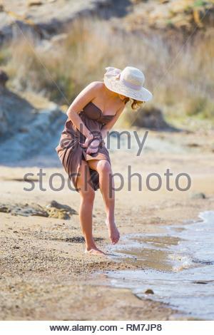 Barefeet on sandy beach walking standing on one leg near sea looking down - Stock Image