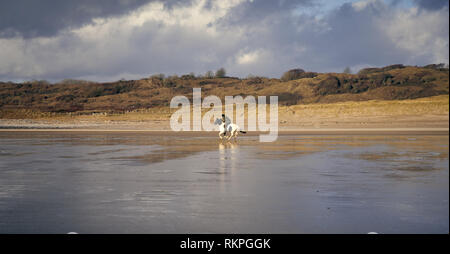 Horse riding on Newton Beach, near Porthcawl, South Wales - Stock Image