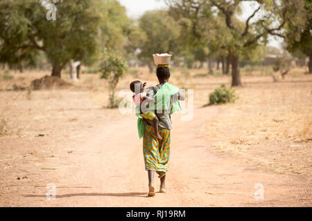 Samba village, Yako Province, Burkina Faso; Sally Zoundi, 35, with her baby Salomon Zoundi, 15 months, on her way to work at the local goldmine to support her family. - Stock Image