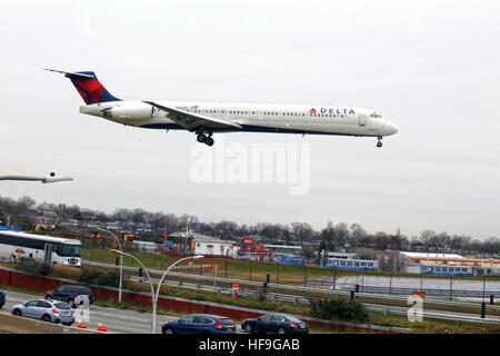 Airplane approaching Laguardia Airport over the Grand Central Parkway, New York, NY, USA - Stock Image