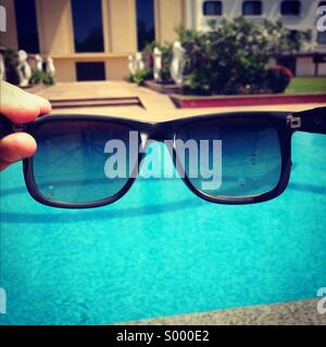 Sunglasses and swimming pool - Stock Image