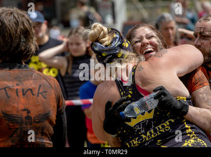 Two women embrace at the end of a mud run - Stock Image