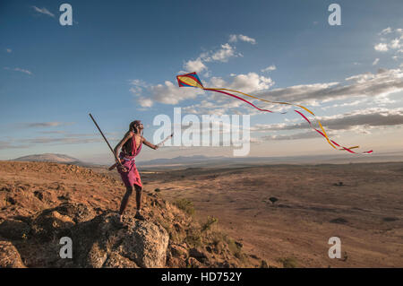 A Maasai warrior flies a kite over a valley with a beautiful landscape in background. Kenya, Africa. - Stock Image