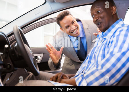 middle aged salesman showing new car interior to customer sitting inside the car - Stock Image