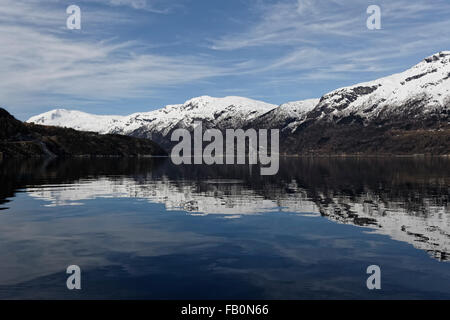 Symmetric reflection of snow covered mountains surrounding the Hardangerfjord in Western Norway. - Stock Image
