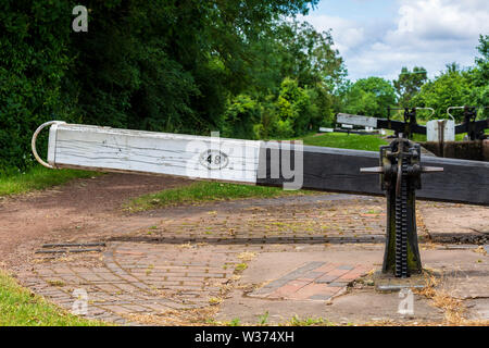 Detail of a lock paddle mechanism with a flight of locks in the background at the Tardebigge Locks, Worcester and Birmingham Canal, Worcestershire - Stock Image