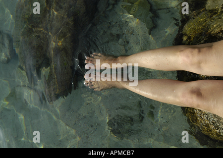 Woman relaxing with her legs on the water Coast beach of Mallorca Majorca Spain Balearic Islands Mediterranean - Stock Image