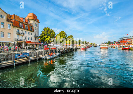 Tourists enjoy the shops, boats and cafes on the Alter Strom canal boardwalk in the town of Warnemunde, Rostock on the northern coast of Germany - Stock Image