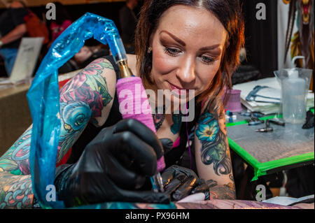 Skibbereen, West Cork, Ireland. 20th Oct, 2018. Tattooist Jen Danger from Canada tattoos the leg of Leah Grobbelaar from Drimoleague during the tattoo show. The show has been attended by many tattooists from across Ireland and the North. The event finishes tomorrow. Credit: Andy Gibson/Alamy Live News. - Stock Image
