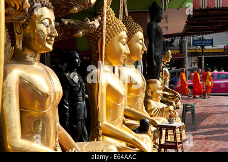 Buddha statues, monks and Tuk Tuk, street scene, Bangkok, Thailand - Stock Image