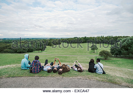 A group of eight young people of mixed ethnicity, some taking selfies.  Photographed in Campbell Park, Milton Keynes, - Stock Image