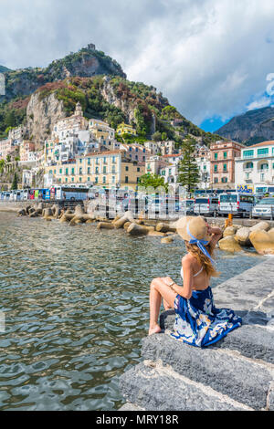 Amalfi, Amalfi coast, Salerno, Campania, Italy. Young woman sitting on the pier of Amalfi village - Stock Image