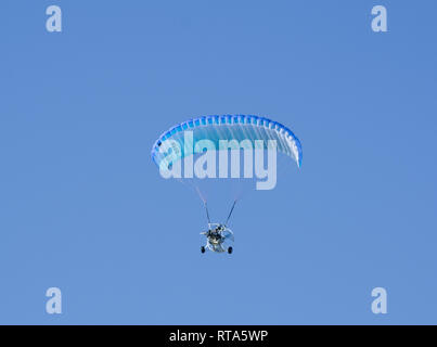 powered paraglider flying under clear blue sky - Stock Image