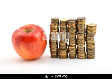 Red apple with coins isolated on white background - Stock Image