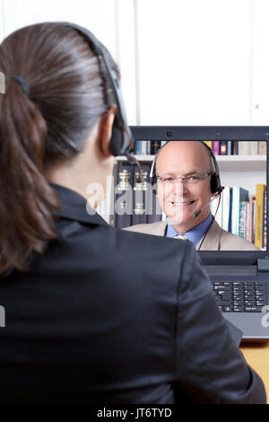 Rear view of a woman in a black blazer with headset in front of a computer, listening to an experienced English teacher, telelearning or e-learning - Stock Image