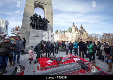 OTTAWA, CANADA - NOVEMBER 11, 2018: soldier putting remembrance poppy in front of a Crowd gathering on National War memorial, on remembrance day to co - Stock Image