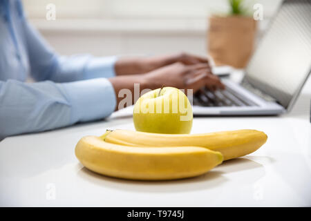 Close-up Of Bananas And Green Apple On Office Desk - Stock Image