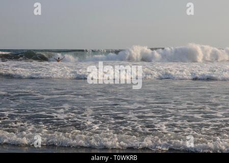 Man standing in ocean holding up his arms with a bit wave about to break on him - Stock Image