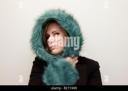 Blonde model in heavy beautiful winter coat with green trim smiling secretly - Stock Image