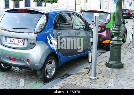 An electric hybrid car being charged on the street in Brussels, Belgium. - Stock Image