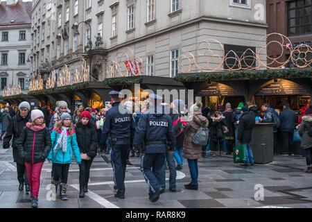 Austrian police walk amongst the crowds at Christmas Market at St Stephens Square, Stephansplatz , Vienna, Austria. - Stock Image