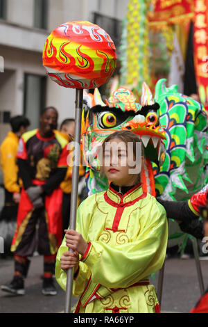 London, UK. 1st January, 2019. A performe from the London Chinese Group ahead of joining the parde at Berkeley Square. About 8,000 performers representing the London boroughs and over 20 countries from across the globe take part on the annual New Years Parade on the street of London on January 1, 2019. The parade will as is custom include dancers, acrobats, cheerleaders, marching bands, historic vehicles and huge balloons making their way from Green Park Tube station to Parliament Square. Credit: david mbiyu/Alamy Live News - Stock Image