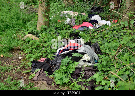 Fly tipped old clothes litter dumped in undergrowth by countryside path - Stock Image