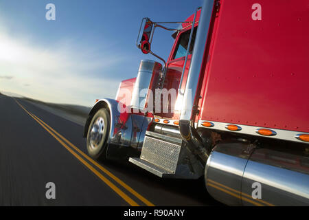 Side view of a Kenworth W900 Class 8 tuck moving on the highway. - Stock Image