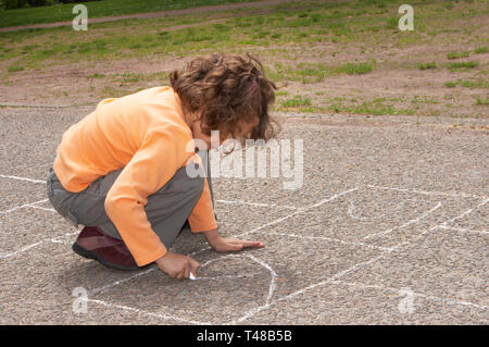 Little girl drawing squares on the street, for hopscotch - Stock Image