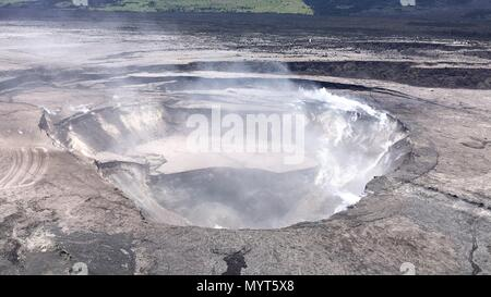 Hawaii, USA. 6th June, 2018. Aerial view of the Halemaumau crater showing collapse of the crater walls enlarging the caldera and deflating the lava lake which once filled the space caused by the eruption of the Kilauea volcano June 6, 2018 in Hawaii. The recent eruption continues destroying homes, forcing evacuations and spewing lava and poison gas on the Big Island of Hawaii. Credit: Planetpix/Alamy Live News - Stock Image