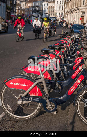TFL Santander sponsored London red rental hire bikes in Southwark Street. Group of commuter cyclists wearing helmets riding by the bike terminal docking station. Transport for London Southwark London UK - Stock Image