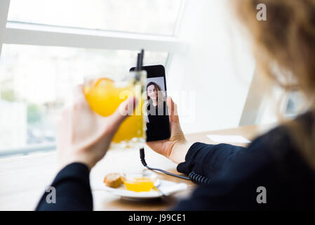 Young trendy woman having a video call with some friend - Stock Image