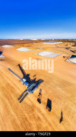Industrial machinery and grain loader at bulk storage warehouse site in the middle of wheat belt artesian basing agricultural region in rural outback  - Stock Image
