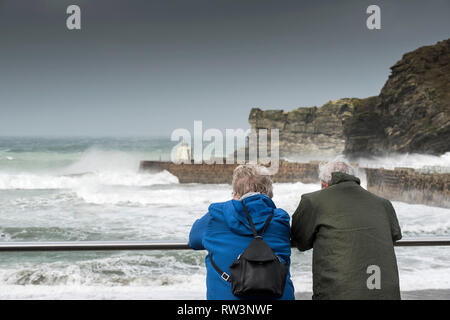 A mature couple watching the rough sea at Portreath in Cornwall. - Stock Image