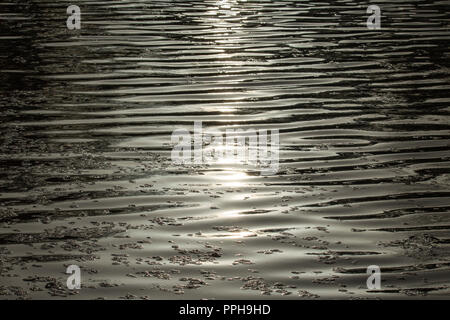 Sunshine in water with shadow lines - Stock Image