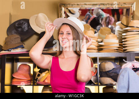 young happy spanish  blonde woman choose straw hat in shop - Stock Image