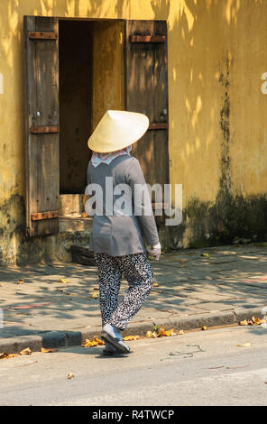 Hoi An a Vietnamese lady walking down a traditional street in Hoi An town Vietnam - Stock Image