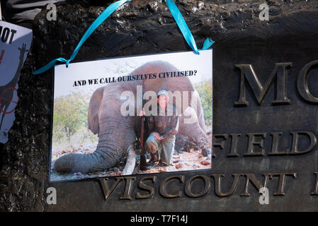 The London March Against Trophy Hunting and Extinction marched through Central London to Downing Street. Placard attached to statue base. - Stock Image