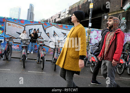 People visiting Brick Lane East End young woman wearing yellow coat strolling along the street in winter in Shoreditch East London E1 UK  KATHY DEWITT - Stock Image