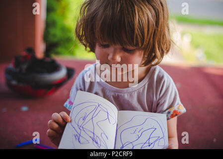 A 3-year old girl showing her mother her artwork. - Stock Image