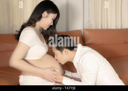 Asian couple pregnant wife and husband kissing on belly woman in bedroom background. - Stock Image