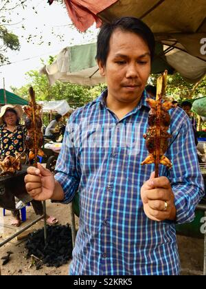 Cambodian local at street food stall with bbq frogs - Stock Image